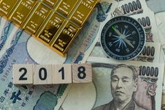 Wooden block with number 2018, gold bullion and compass on pile. Of japanese yen banknotes as year 2018 financial safe haven or tax concept Royalty Free Stock Photo