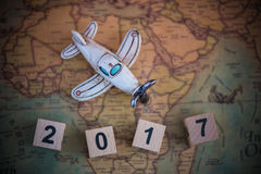 Wooden block with toy plan on world map. Concept new year 2017 Royalty Free Stock Photos