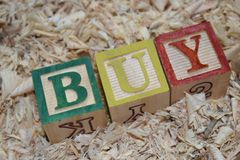 BUY. Wooden block with word BUY placed in the wooden saw dust royalty free stock photos