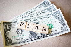Wooden block word PLAN and Dollar banknote Stock Photography
