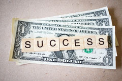 Wooden block word success and Dollar banknote Stock Photography