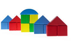 Wooden blocks concept: Being diffferent. Row of plain houses built with wooden toy blocks with one house in the middle being different than the rest Royalty Free Stock Photo