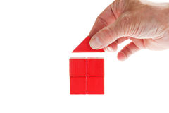 Wooden blocks concept: Finishing the house. House built with wooden toy blocks with someone putting the roof on top to finish the building Royalty Free Stock Photography