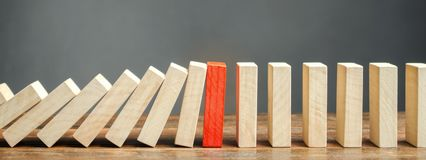 Wooden blocks and the effect of dominoes. Risk management concept. Successful strong business and problem solving. Reliable leader. Stop the destructive stock images