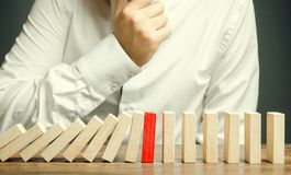Wooden blocks and the effect of dominoes. Risk management concept. Successful strong business and problem solving. Reliable leader. Stop the destructive royalty free stock images