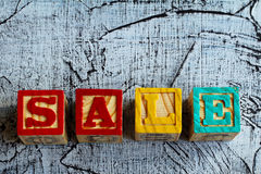 Wooden blocks with the letters `sale`. And an aged  background Royalty Free Stock Image