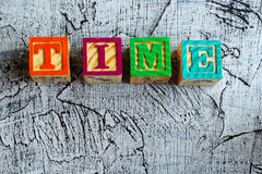 Wooden blocks with the letters `time`. And an aged  background Stock Images
