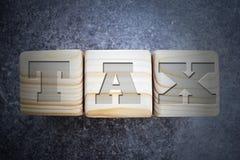 Tax - text on wood texture blocks on dark grey background. stock image