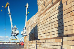 Wooden blocks on the loading at the port with cranes Stock Photos