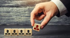 Wooden blocks with a picture of workers. the businessman or CEO removes / dismisses the employee. management within the team. stock photography