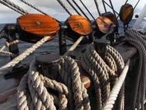 Wooden blocks or pulleys on traditional sailing vessel. Closeup of wooden blocks and lines on traditional tallship royalty free stock image