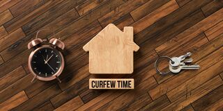 Wooden blocks in shape of a house with text CURFEW TIME