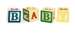 Wooden blocks spelling baby. Closeup of wooden toy alphabet blocks spelling word baby, isolated on white background Stock Image
