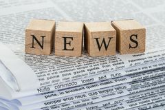 Wooden blocks spelling news on newspapers Stock Photography