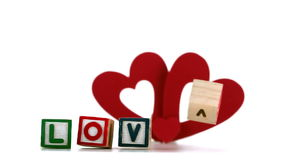 Wooden blocks spelling out love falling over with heart ornament Stock Photos