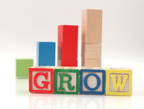 Wooden Blocks Spelling Word Grow. Set of childrens blocks spelling the word grow with graph representing growth in background Royalty Free Stock Photography