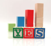 Wooden Blocks Spelling Word Yes. Set of childrens blocks spelling the word yes with graph representing growth in background Stock Image