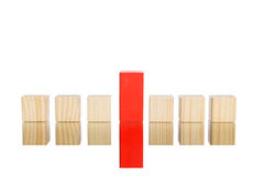 Wooden blocks standing in line with blue one in the centre Stock Photo