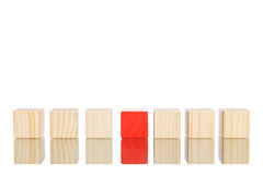 Wooden blocks standing in line with blue one in the centre Royalty Free Stock Photos
