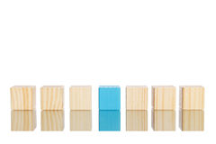 Wooden blocks standing in line with blue one in the centre Stock Photos