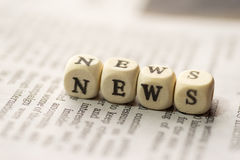 Wooden blocks with the text, NEWS, on the newspaper Royalty Free Stock Photo