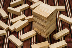 Wooden blocks tower and block spread around stock image
