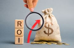 Wooden Blocks With The Word ROI And The Up Arrow With The Money Bag. High Level Of Business Profitability. Return On Investment, Royalty Free Stock Images