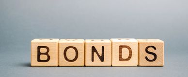 Wooden blocks with the word Bonds. A bond is a security that indicates that the investor has provided a loan to the issuer. stock images