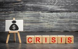 Wooden blocks with the word Crisis and the image of dollars. The concept of financial and economic crisis. capital outflow. Wooden blocks with the word Crisis royalty free stock photos