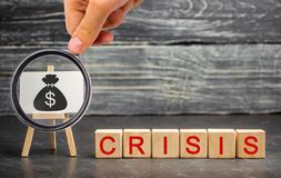 Wooden blocks with the word Crisis and the image of dollars. The concept of financial and economic crisis. capital outflow. Wooden blocks with the word Crisis stock photo