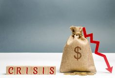 Wooden blocks with the word Crisis and money bag. The concept of financial and economic crisis. capital outflow. sabotage of the. Economy. bankruptcy. cash loss royalty free stock image