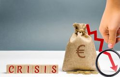 Wooden blocks with the word Crisis and money bag. The concept of financial and economic crisis. capital outflow. sabotage of the. Economy. bankruptcy. cash loss royalty free stock photo