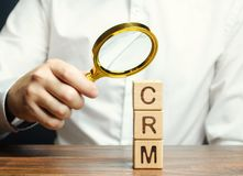 Wooden blocks with the word CRM Customer Relationship Management and businessman. Automation strategies for interacting with. Clients. Increase sales, optimize stock image