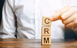 Wooden blocks with the word CRM Customer Relationship Management and businessman. Automation strategies for interacting with. Clients. Increase sales, optimize stock photo