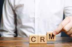 Wooden blocks with the word CRM Customer Relationship Management and businessman. Automation strategies for interacting with. Clients. Increase sales, optimize stock photography