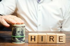 Wooden blocks with the word Hire and dollars. The offer of the salary level at the interview. Raise wages. Transition to a higher stock images