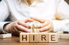 Wooden blocks with the word Hire. Headhunter selects a person from the crowd. Good choice. Human Resource Management. Recruiting. Headhunting. Hiring employees royalty free stock photography