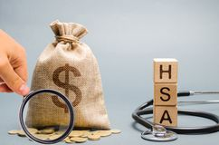 Wooden blocks with the word HSA and money bag with stethoscope. Health savings account. Health care. Health insurance. Investments. Tax-free medical expenses stock photo