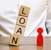 Wooden blocks with the word Loan fall on a miniature person. The concept of large lending rates for property and business. Lending