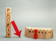 Wooden blocks with the word Profit, down arrow and business team. Unsuccessful business and bankruptcy. Profit decline. Loss of. Investment. Economic crisis stock images