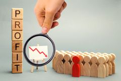 Wooden blocks with the word Profit, down arrow and business team. Unsuccessful business and bankruptcy. Profit decline. Loss of. Investment. Economic crisis stock image