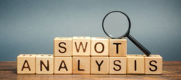 Wooden blocks with the word SWOT analysis and a magnifying glass. The method of strategic business planning. Strengths, weaknesses