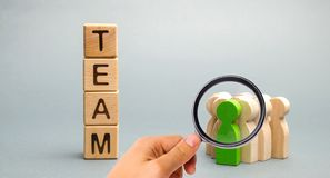 Wooden blocks with the word Team and a crowd of workers with a leader. The concept of a strong reliable business team. Teamwork. Team management. Choosing a royalty free stock photo