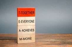 Wooden blocks with the word Together, Everyone, Achieves, More. Teamwork and team concept. Community, support, partnership.