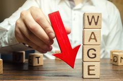 Wooden blocks with the word Wage and red arrow down. Salary reduction. Drop in profits. Financial crisis. Demote. Low profit. Capital outflow. Concept of royalty free stock photo