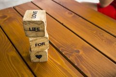 Wooden blocks with the words lie on the table. Wooden cubes with letters and symbols. Life for love. Wooden blocks with the words lie on the table. Wooden cubes royalty free stock photo