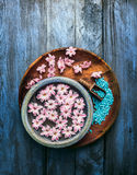 Wooden and blue bowl with pink flowers and water,  scoop with sea salt on old background Stock Images