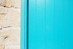 Wooden blue plank door texture near stone wall. Royalty Free Stock Photography