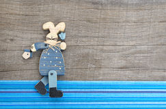 Wooden blue rabbit decoration on grey wooden background with blu Royalty Free Stock Images