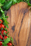 Wooden board background, fresh lettuce and tomatoes Stock Photo